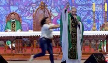Mulher empurra Padre Marcelo de cima do altar.